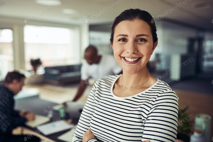 Smiling young businesswoman at work with colleagues in the background