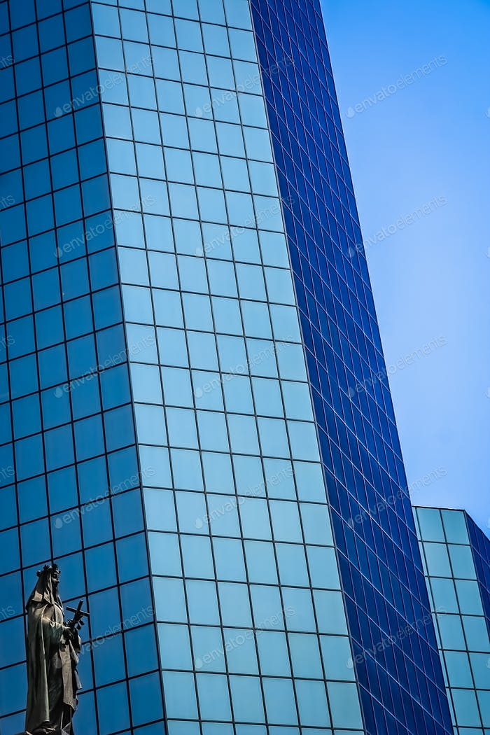 Statue of holy Mary in front of modern glass office building in