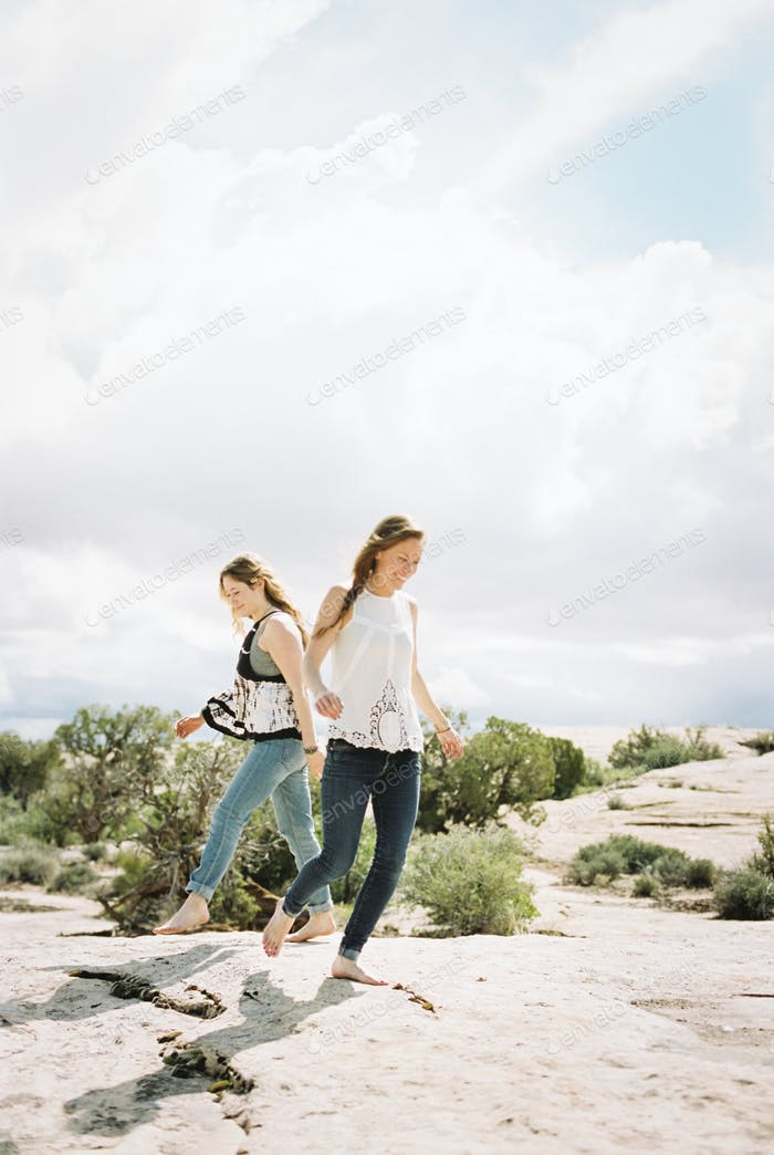 Two women with bare feet, running and dancing in the open space