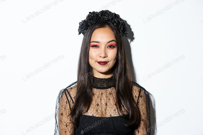 Image of smiling devious young witch looking at camera with cunning smirk, standing over white