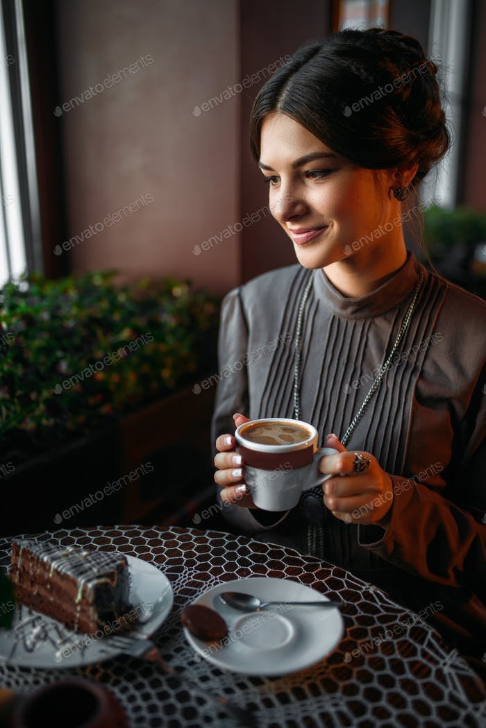 A young girl with a cup of coffee in retro cafe