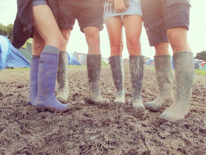 Nahaufnahme von Freunden in Gummistiefel Walking To Festival