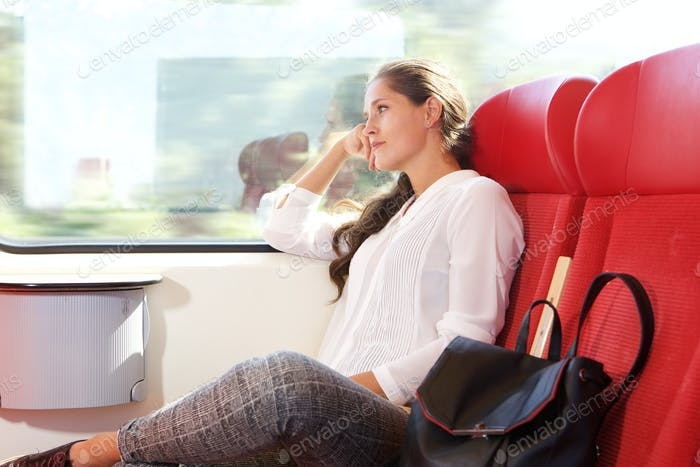 beautiful woman traveling by train looking out the window