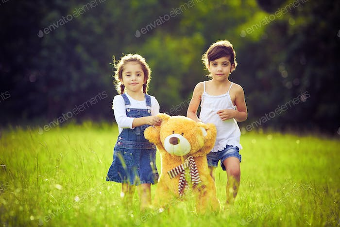 Two little girls in the grass with teddy bear