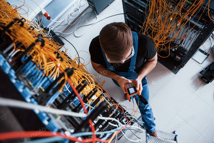 Young man with measuring device that works with internet equipment and wires in server room