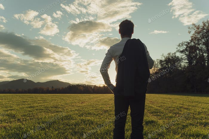 Young businessman standing in autumn meadow gazing into the future