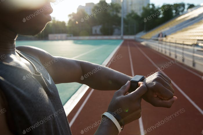 Cropped image of a young african athlete using wrist smartwatch