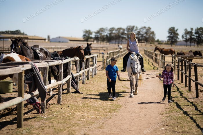 Kids riding a horse in the ranch