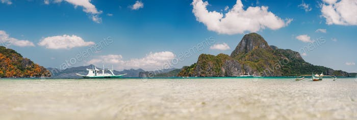 Cadlao island background with filippino traditional boats in shallow bay at El Nido bay from low