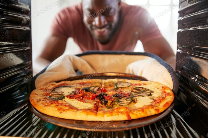 View Looking Out From Inside Oven As Man Cooks Fresh Pizza