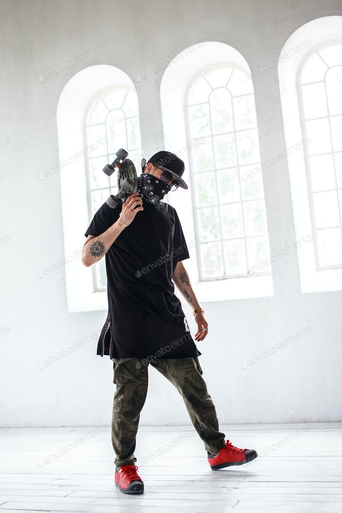 Man in a mask and black clothes holds skateboard.