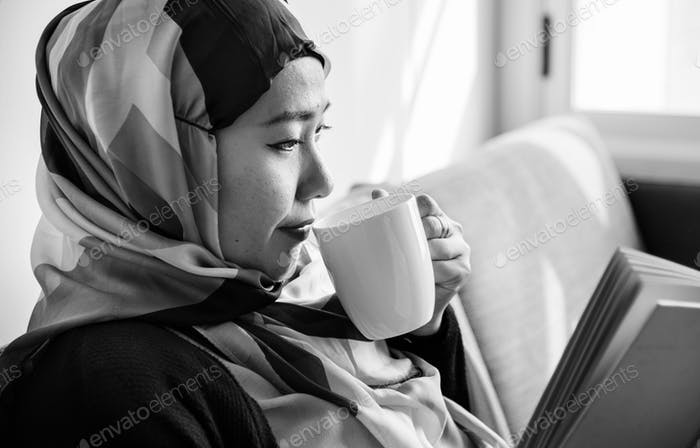 Islamic woman reading and drinking coffee