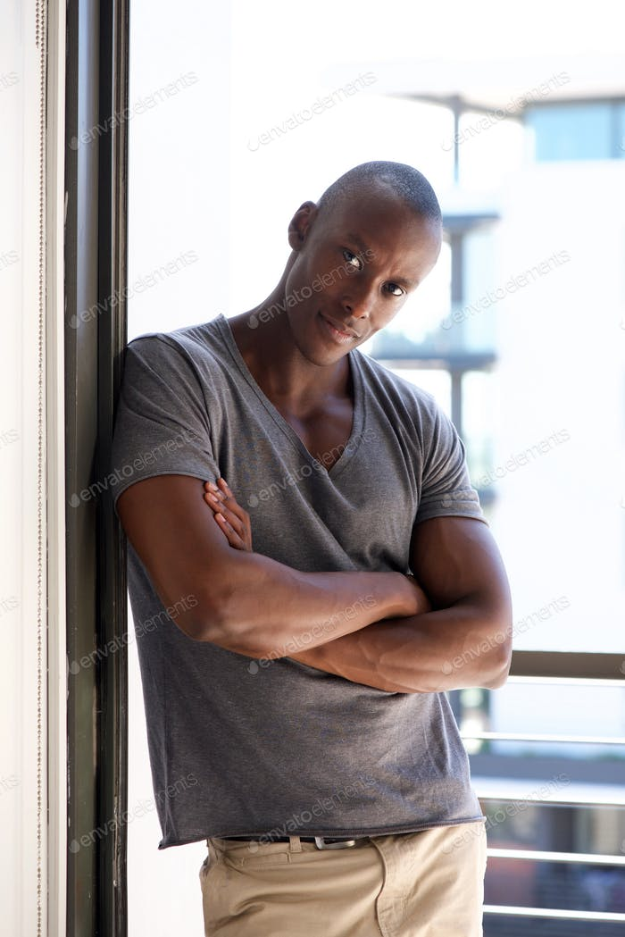 cool african american man leaning against wall by window