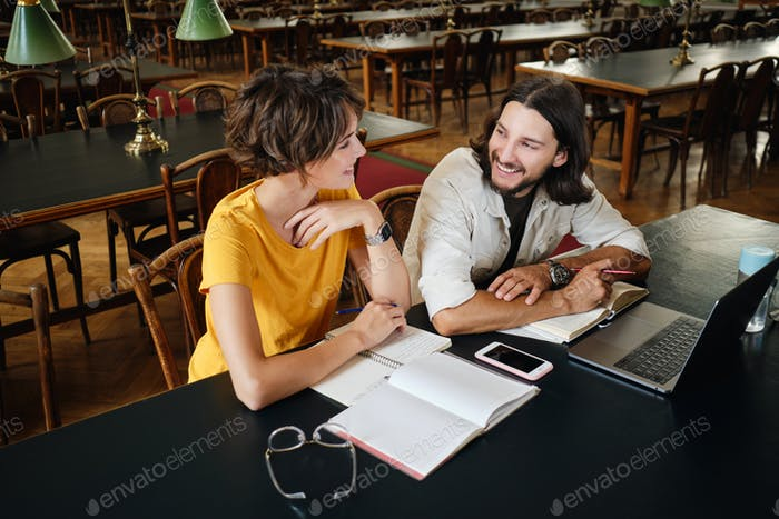 Couple of attractive students happily studying together in library of university