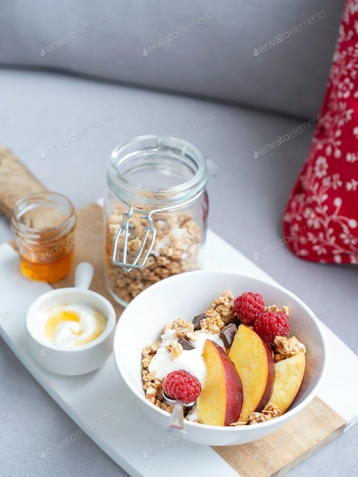 Bowl of homemade granola with yogurt, honey, fresh raspberries