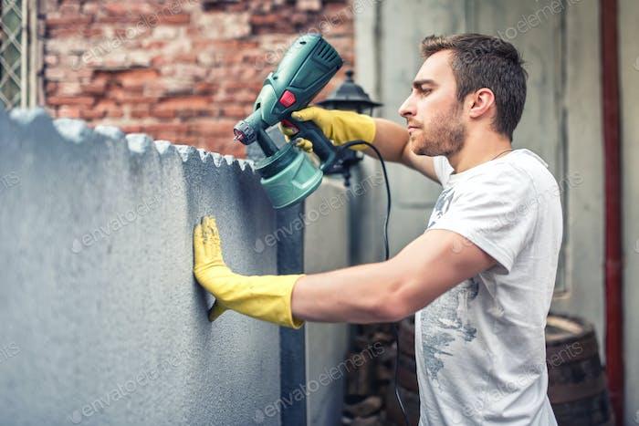 Человек с помощью защитных перчаток окрашивают серую стену с распылительной краской пистолетом. Молодой рабочий ремонт дома