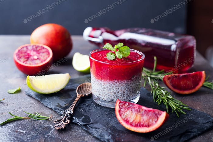 Chia pudding with fresh berries puree and honey with slice citrus on slate dark background
