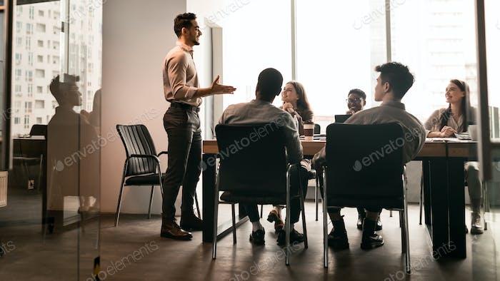 Colleagues having meeting in board room, businessman giving speech