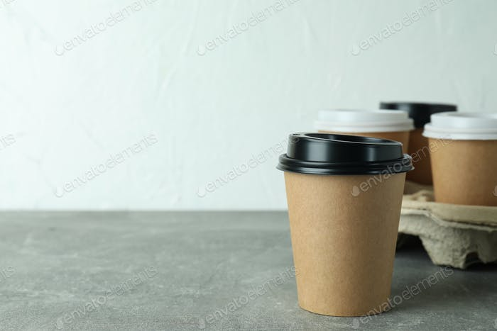 Cup holder with coffee cups on gray textured table