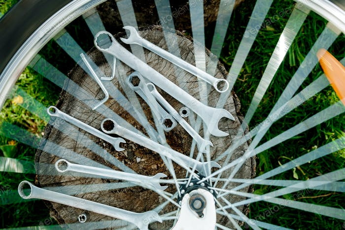Tools, instrument for repairing bike on the wooden background outdoor wheel. Bicycle repair.