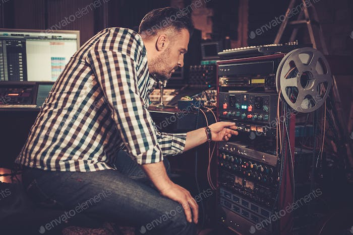 Sound engineer working with professional audio equipment in the boutique recording studio.