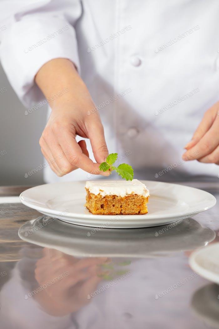 Female fhef decorate dessert cake with lemon leaf