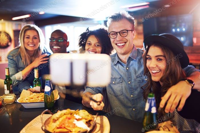 Happy group of people selfies in bar