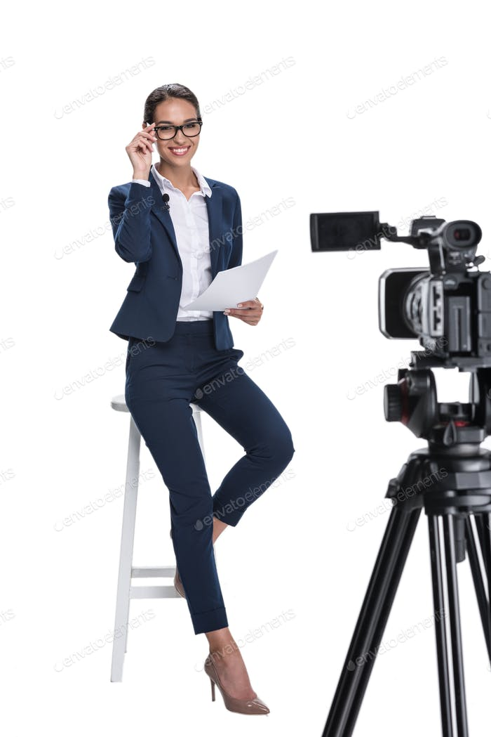 beautiful smiling female newscaster with papers smiling and sitting in front of camera, isolated on
