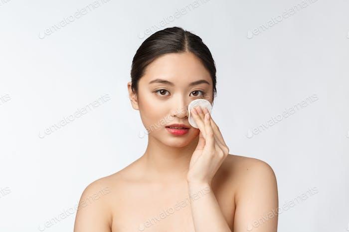 skin care woman removing face makeup with cotton swab pad - skin care concept. Facial closeup of