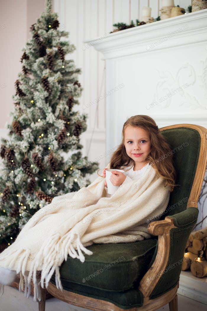 Little girl wearing pajama sitting on armchair wrapped in a blanket with holiday bedding by