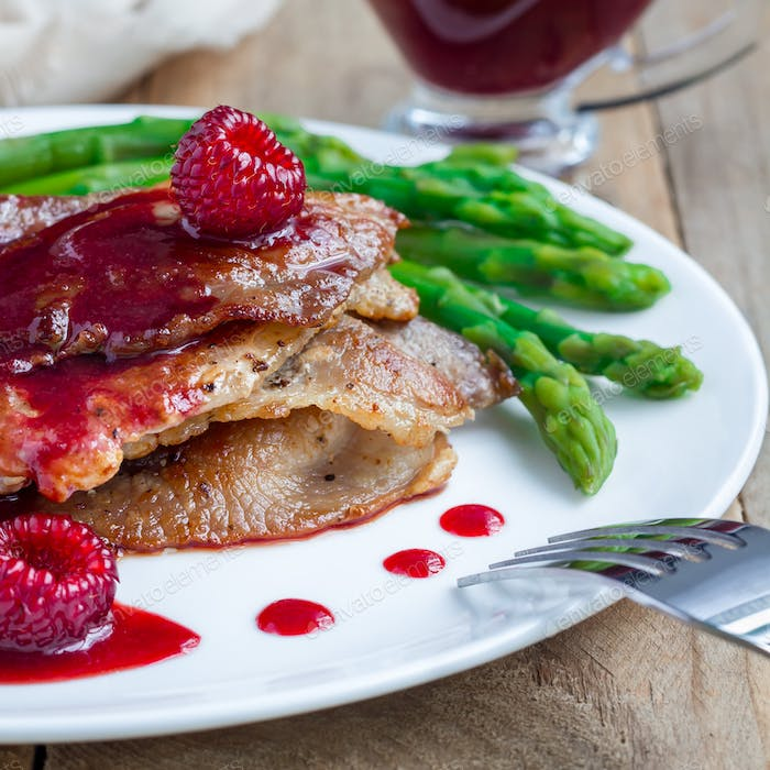 Pork cutlets with raspberry sauce and asparagus on white plate, square
