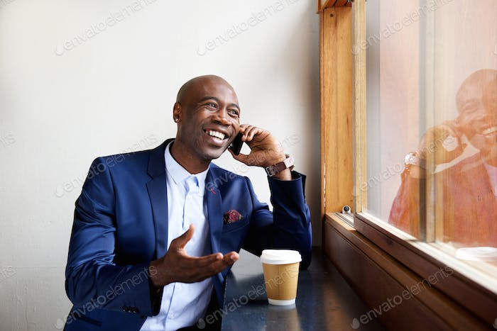 Happy businessman at a cafe talking on cell phone