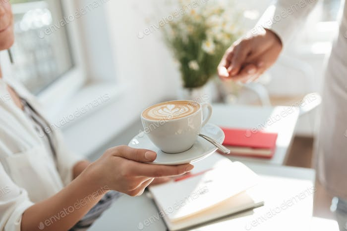 Close up of woman hand taking coffee cup from man hand in coffee shop