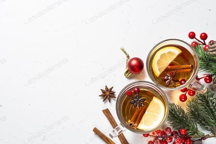 Winter heißer Tee mit Früchten, Beeren und Gewürzen auf weißem Tisch