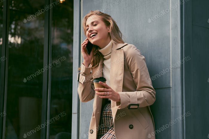 Smiling blond girl in stylish trench coat with coffee to go happily talking on cellphone outdoor
