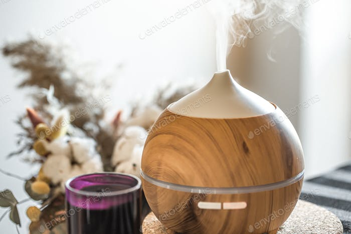 Modern oil aroma diffuser close up on a blurred background.
