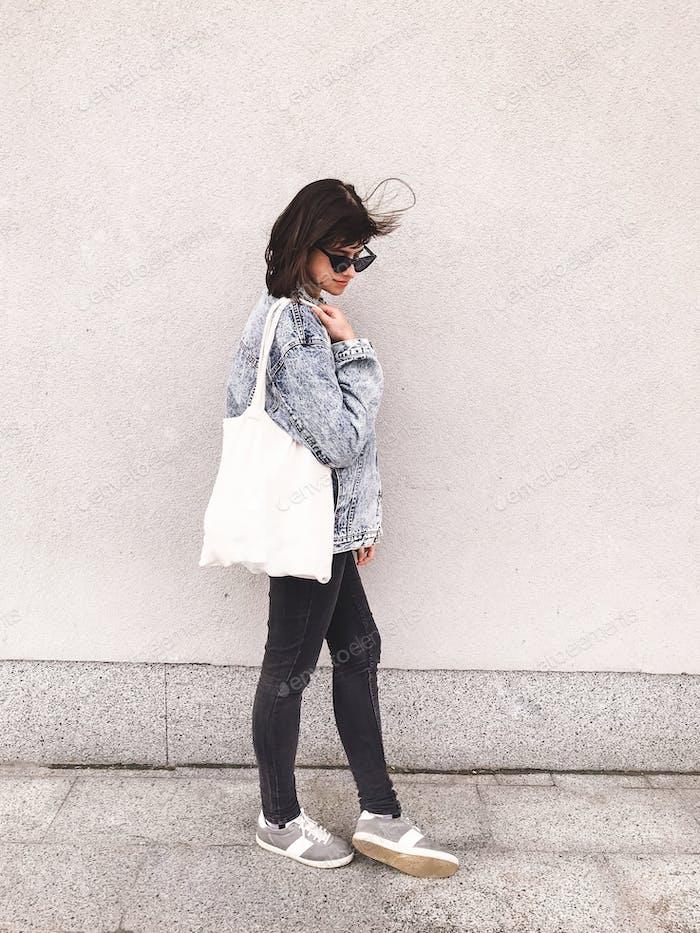Stilvolles Hipster-Mädchen in Jeans-Outfit und Tragetasche posiert in der Stadt Straße auf dem Hintergrund der Wand