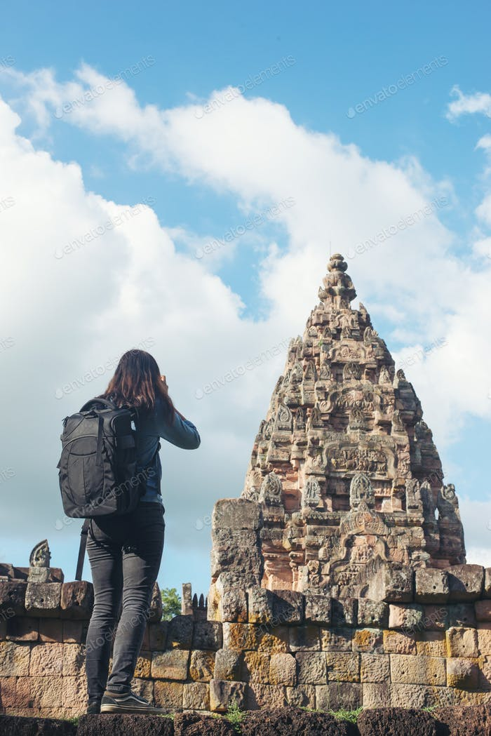 Young woman tourist with backpack coming to shoot photo at ancient phanom rung temple in thailand.