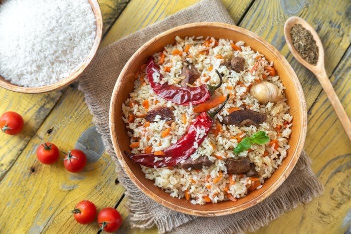 Bowl of pilaf on the wooden table
