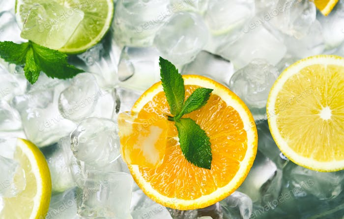 Fresh citrus fruits with mint on ice cubes