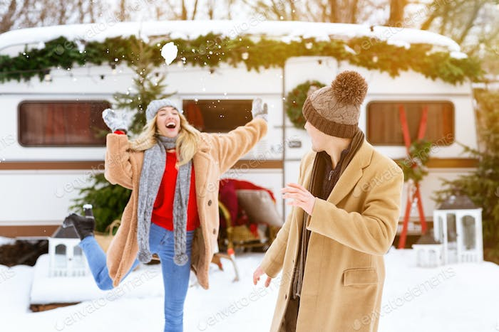 Cheerful Girl Having Snow Fight With Boyfriend During Winter Day At Camping