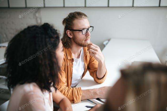 Portrait of young man with blond hair and beard dreamily looking aside while sitting with сolleagues