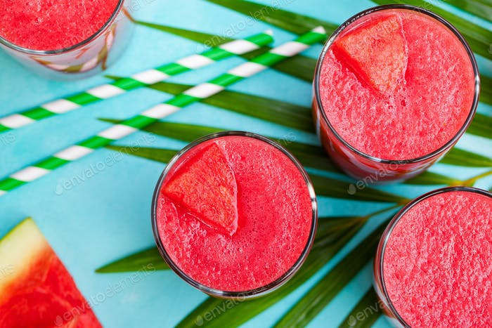 Watermelon Smoothie, Fresh Juice on Blue Background with Palm Leaf. Top View.
