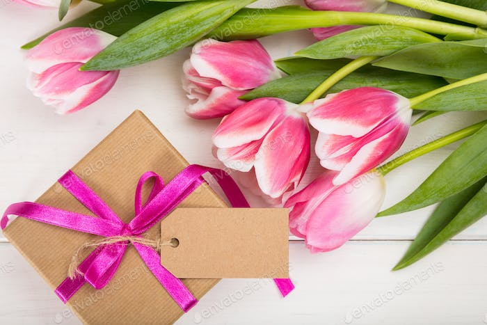 Mothers day. Pink tulips and a blank card gift on white background, top view, copy space