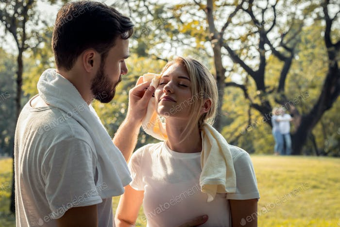 Young couples are wiping sweat after exercising.