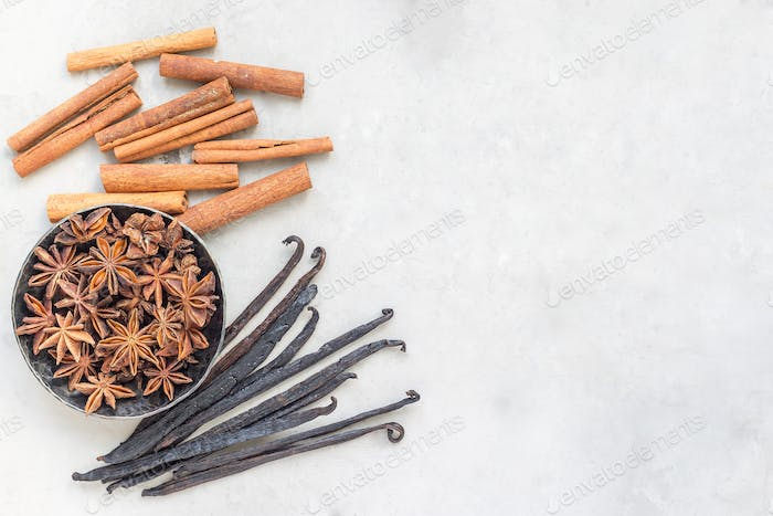 Aromatic winter spices on gray concrete background, top view, copy space, horizontal