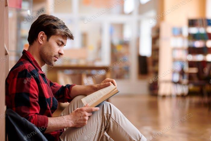 Lässige junge Mann lesen Buch während sitzen durch Bücherregal