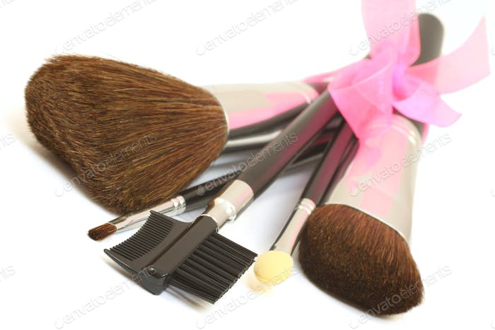 Make-up brushes with pink bow isolated over white