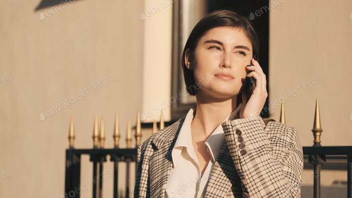 Young beautiful lady talking on phone waiting business meet on city street. Always in touch