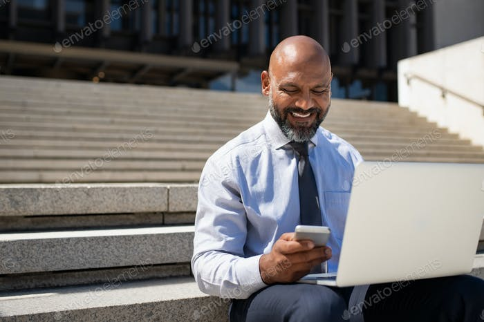 Businessman sitting on stairs and working on laptop